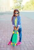 Forme al niño de la niña con las gafas de sol que llevan del monopatín y la camisa a cuadros del inconformista Fotos de archivo