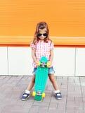 Forme al niño de la niña con las gafas de sol que llevan del monopatín y la camisa a cuadros en ciudad Imagen de archivo