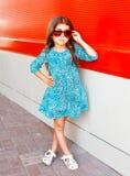 Forme al niño de la niña en gafas de sol y un vestido del leopardo Fotos de archivo