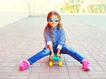 Forme al niño de la niña que se sienta en el monopatín en ciudad Fotos de archivo libres de regalías