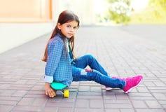 Forme al niño de la niña que se sienta en el monopatín en ciudad Imágenes de archivo libres de regalías