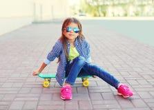 Forme al niño de la niña que se sienta en el monopatín en ciudad Fotografía de archivo