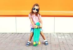 Forme al niño elegante de la niña con las gafas de sol que llevan del monopatín y la camisa a cuadros en ciudad Fotos de archivo