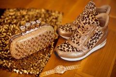Forme as sapatilhas do leopardo com o relógio de pulso e a bolsa dourados do encanto no fundo de madeira Foto de Stock Royalty Free