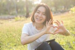 Forme asiatique thaïlandaise mignonne de coeur d'amour de fille avec ses mains Photos stock