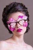 Forme a beleza a menina modelo que veste os vidros à moda completos das pétalas cor-de-rosa Composição e penteado creativos imagem de stock royalty free
