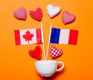 Forme bianche del cuore e della tazza con le bandiere del Canada e della Francia Fotografia Stock Libera da Diritti