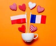 Forme bianche del cuore e della tazza con le bandiere della Polonia e della Francia Fotografie Stock