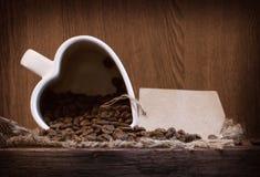 Forme blanche de tasse de coeur avec des grains de café Photographie stock