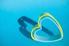 Forme bleue et jaune de coeur sur le fond bleu, symbole d'amour Photographie stock libre de droits