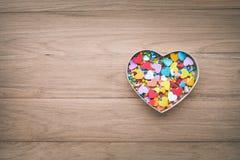 Forme colorée de coeur dans la boîte sur le fond en bois de table Image stock