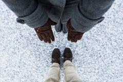 Forme a composição de luvas marrons fêmeas e das botas marrons ocasionais masculinas que estão na superfície corajoso coberta asf Foto de Stock