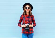 Forme a controles sonrientes bastante jovenes de la mujer la cámara retra que lleva el sombrero negro camisa a cuadros roja sobre Foto de archivo libre de regalías