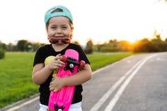 Forme a criança da menina com vestir do skate óculos de sol e camisa do moderno fotos de stock royalty free