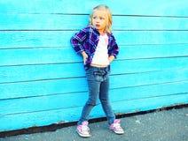 Forme a criança da menina o levantamento modelo em um fundo azul imagens de stock