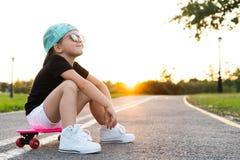 Forme a criança da menina que sentam-se no skate na cidade, vestir óculos de sol e o t-shirt fotografia de stock
