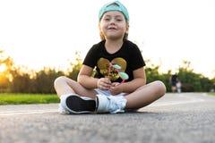 Forme a criança da menina que veste um tampão e um t-shirt que sentam-se na cidade fotografia de stock royalty free