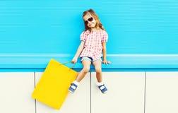 Forme a criança fresca com o saco de compras no fundo azul colorido fotografia de stock royalty free