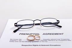 Forme d'accord prénuptial et deux anneaux de mariage Photo stock