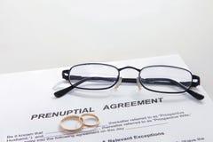 Forme d'accord prénuptial et deux anneaux de mariage Photographie stock libre de droits