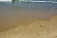 Forme d'amour et de coeur écrite sur le littoral Images stock