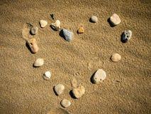 Forme d'amour sur le sable Photographie stock