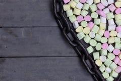 Forme d'amoureux des guimauves avec la chaîne en métal sur le fond en bois, la décoration pour l'amour et le concept de Saint Val Photographie stock