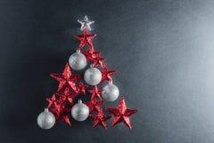 Forme d'arbre de Noël avec des étoiles de rouge et des babioles argentées Image libre de droits