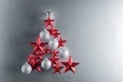 Forme d'arbre de Noël avec des étoiles de rouge et des babioles argentées Photo stock