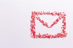 Forme d'enveloppe sur le fond blanc fait de bonbons blancs et roses rouges à coeurs Vue supérieure Jour de Valentine Concept d'am photo libre de droits