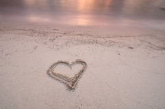 Forme de coeur écrite sur une plage Image stock