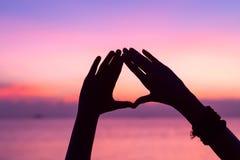 Forme de coeur avec des mains au fond de coucher du soleil Image libre de droits