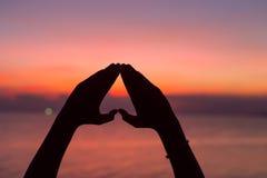 Forme de coeur avec des mains au fond de coucher du soleil Image stock