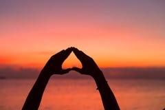 Forme de coeur avec des mains au fond de coucher du soleil Photographie stock libre de droits
