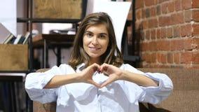 Forme de coeur avec des mains par la jeune belle fille s'asseyant sur le sofa Photos libres de droits