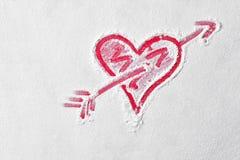 Forme de coeur avec la flèche de cupidon en farine sur le conseil rouge Signe d'amour Photo libre de droits