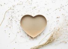 Forme de coeur avec la fleur sèche de branche sur le fond blanc Photo stock