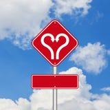 Forme de coeur avec le panneau routier de flèche Images stock