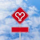 Forme de coeur avec le panneau routier de flèche Photos stock