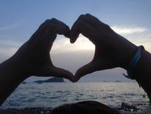 Forme de coeur avec les doigts humains et le coucher du soleil Photographie stock