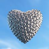 Forme de coeur composée de beaucoup de ballons de football avec l'éclairage dramatique Image de haute résolution Photos stock