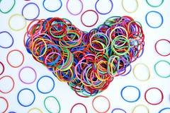 Forme de coeur d'anneau en caoutchouc coloré sur le fond de livre blanc Image stock