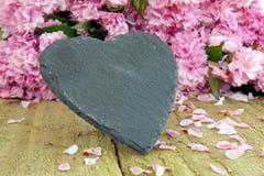 Forme de coeur d'ardoise avec la fleur rose Image libre de droits