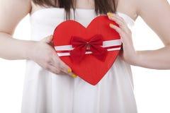 Forme de coeur dans des heands d'une fille d'isolement sur le blanc Photo stock