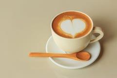 Forme de coeur dans la tasse de café chaude de cappuccino Photo stock