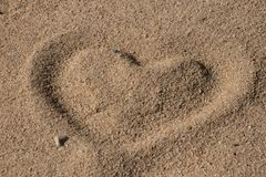 Forme de coeur dans le sable photos stock