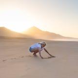 Forme de coeur de dessin de Madame en sable sur la plage Image libre de droits