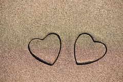 Forme de coeur de deux sables dans le sable par la mer Photos libres de droits