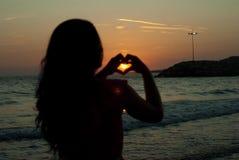 Forme de coeur de femme par coucher du soleil Photo stock