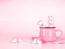 Forme de coeur de guimauve dans la tasse sur le fond rose avec amour concentré Photos stock